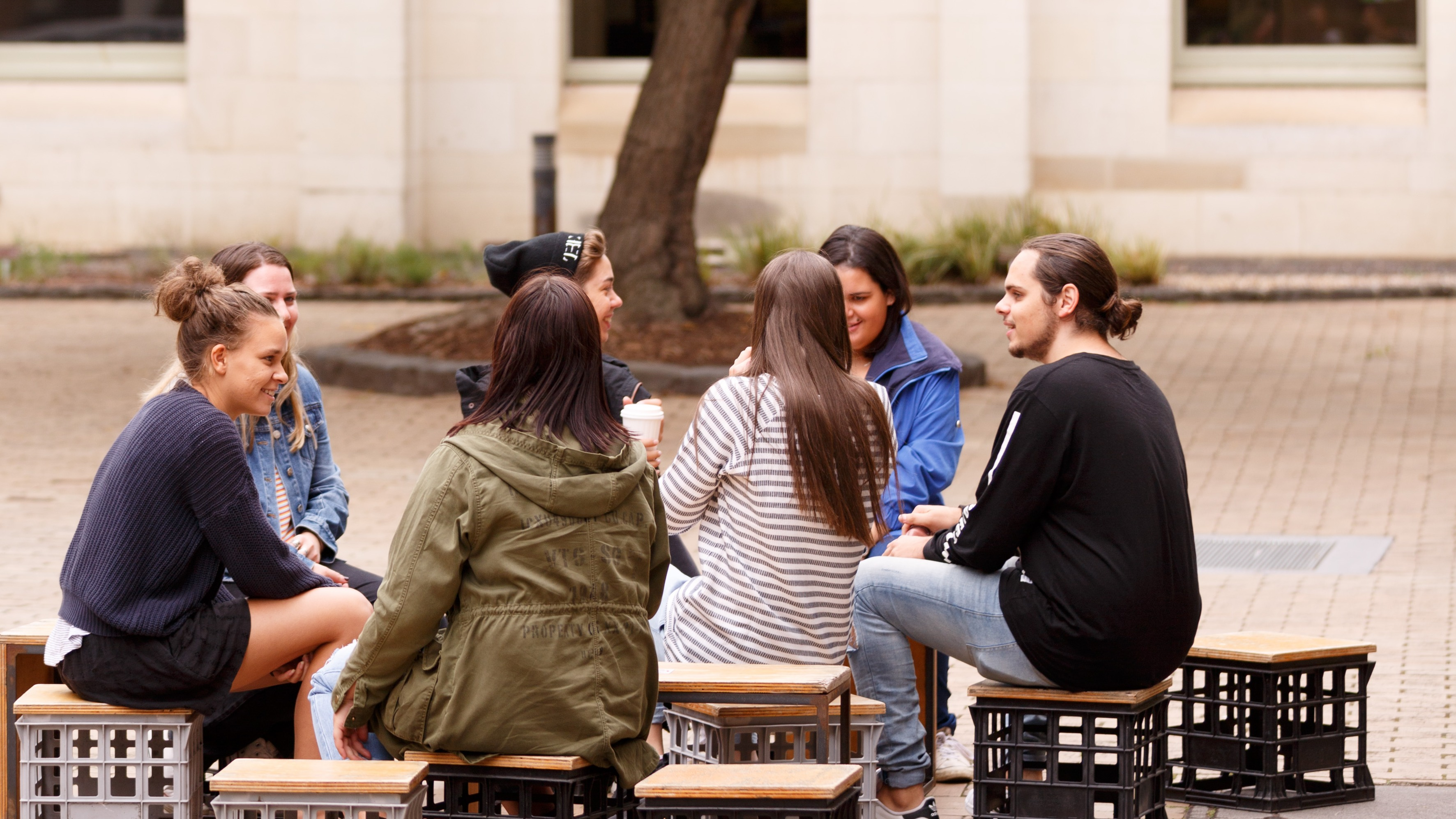 Students sitting in a circle on milk crates