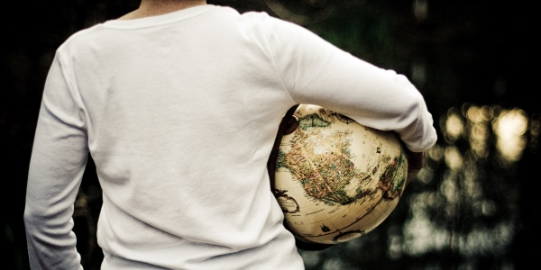 Person holding a world globe under arm